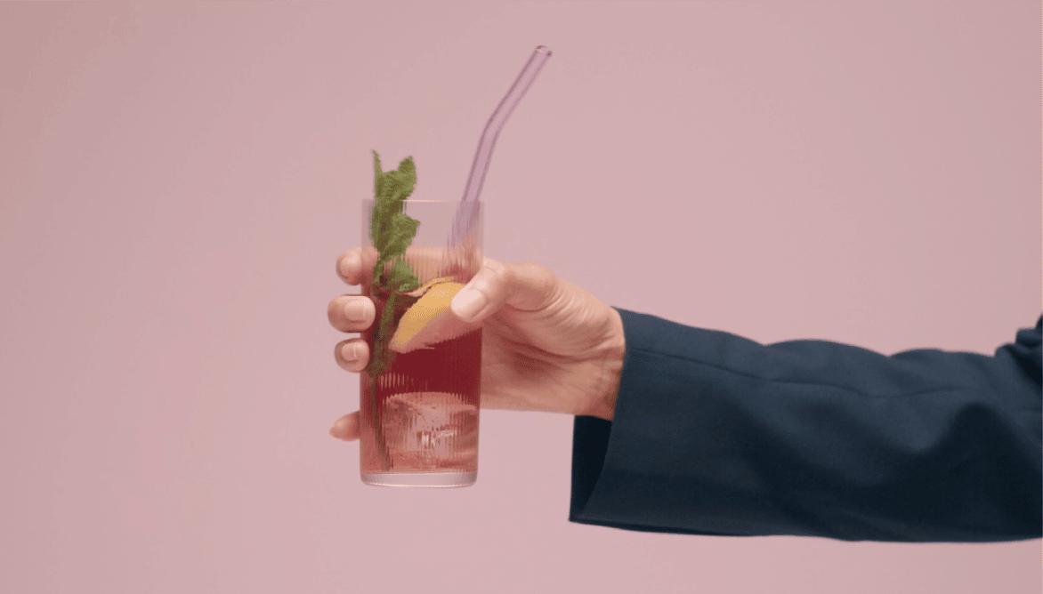 Genom att signera dokument digitalt kan du exempelvis skicka in din ledighetsansökan digitalt. Bild visar hand med drink och rosa bakgrund.
