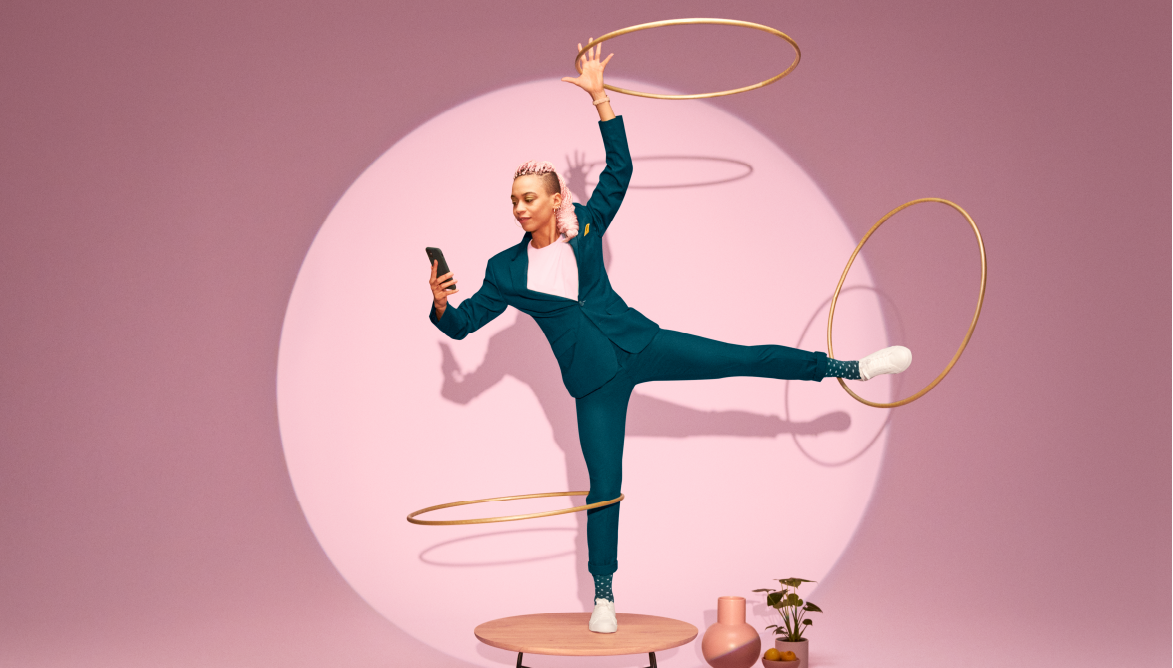 Woman looking at her phone while doing hula hoop with her other arm and legs. Image symbolising the flow of a data driven sales strategy and approach.