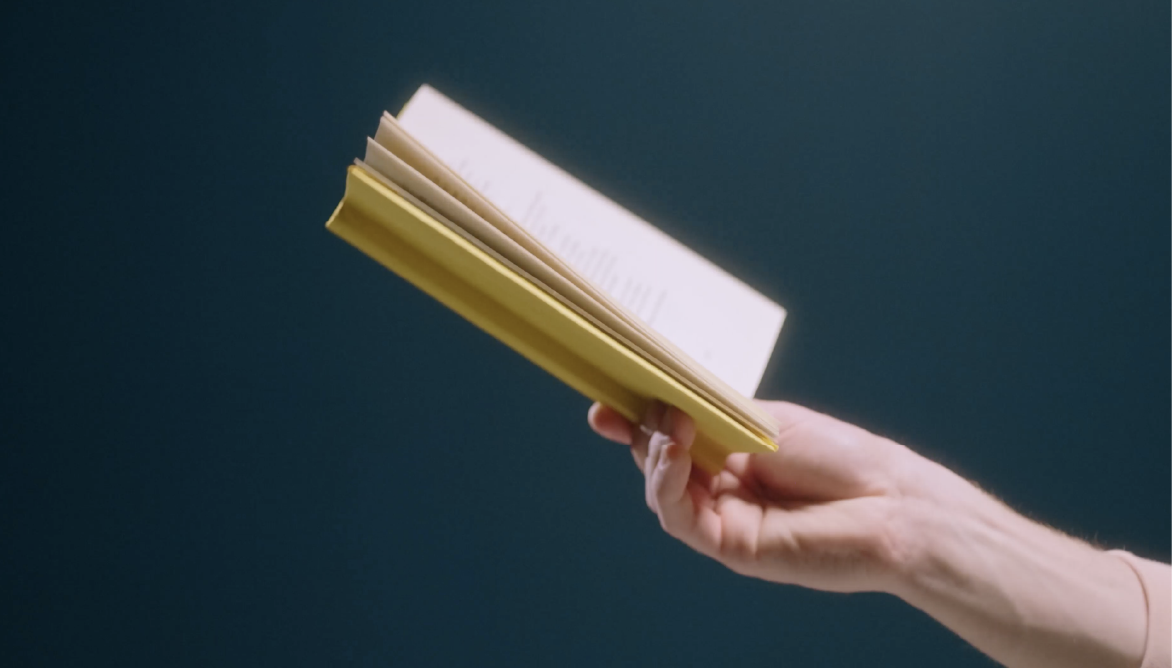 Hand holding a yellow book symbolising reading more of our articles on sales proposals and agreements.