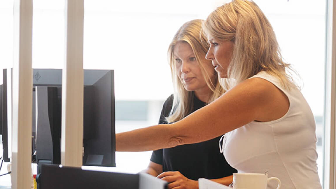 two women looking at a computer