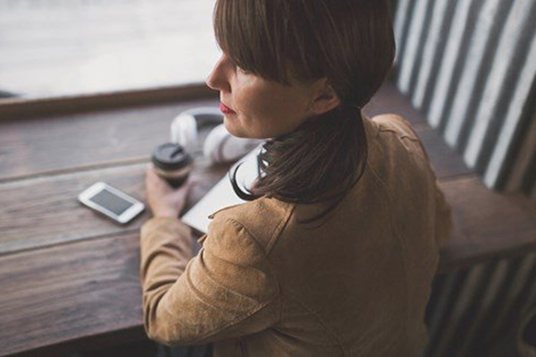 previa is using Oneflow. Image of woman holding coffee and looking out a window