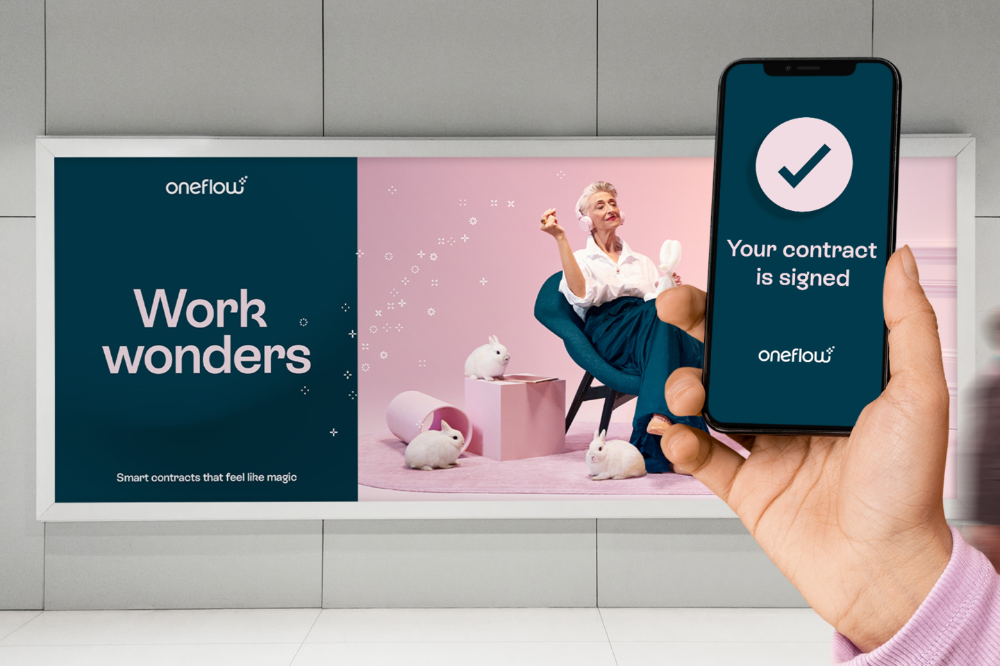 Picture of a hand holding a phone with screen showing that a contract has been signed through Oneflow. The background  showing a subway billboard for Oneflow, symbolising you can sign contracts wherever you are.