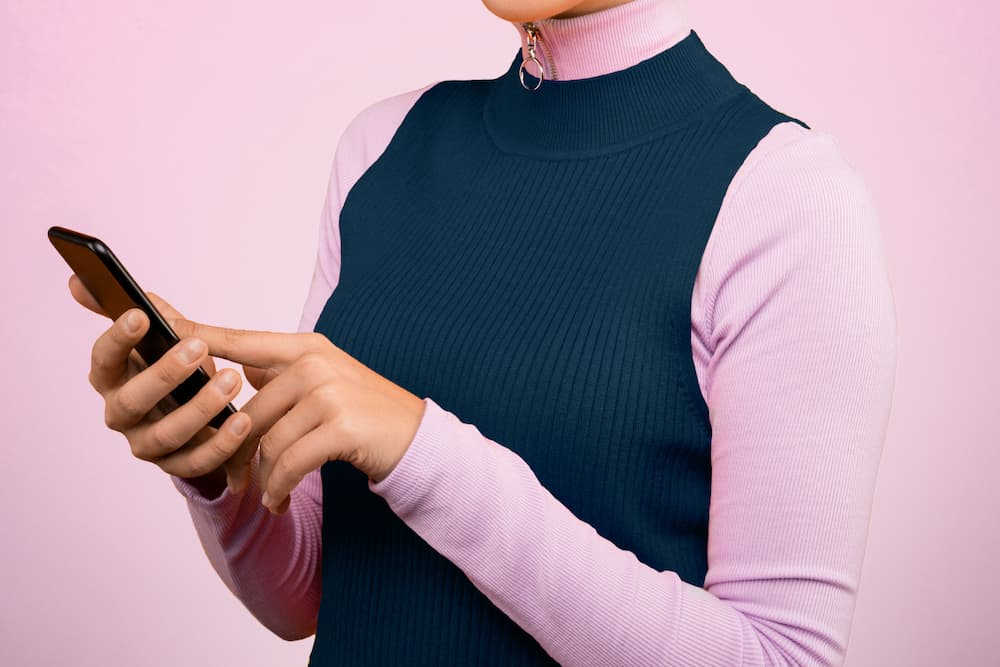 Person wearing a pink long sleeve t-shirt and blue vest is looking at her phone and signing a contract online legally binding signature